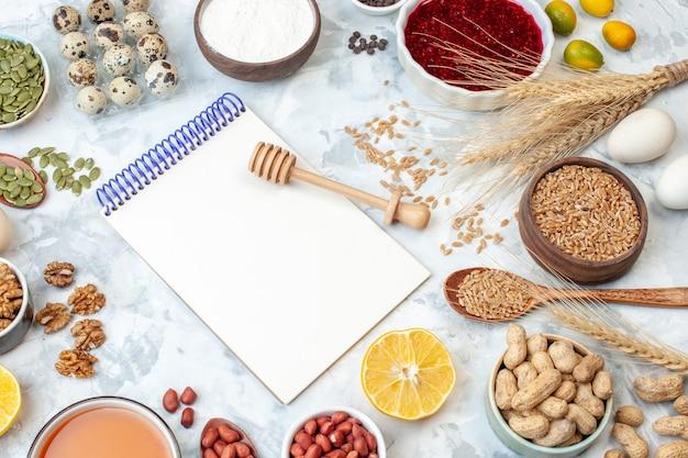 正面図開いたメモ帳卵小麦粉ゼリー白い背景の上のさまざまなナッツと種子ナッツ色ケーキ甘いパイ写真砂糖生地