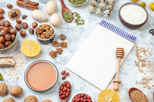 正面図開いたメモ帳と卵粉ゼリー白い背景にさまざまなナッツと種子ナッツ生地色ケーキ甘いパイ写真砂糖