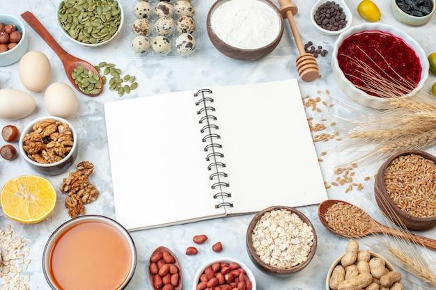 正面図開いたメモ帳、白い背景にゼリーの卵のさまざまなナッツと種子生地の色ケーキ甘い砂糖パイナッツハートの写真