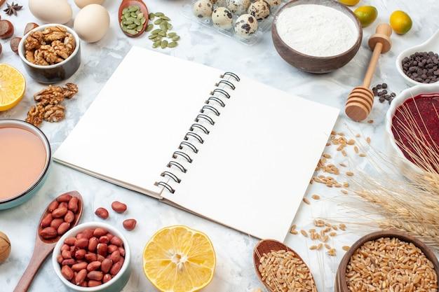 正面図開いたメモ帳、白い背景にゼリーの卵のさまざまなナッツと種子生地の色ナッツケーキ甘いパイハート写真砂糖