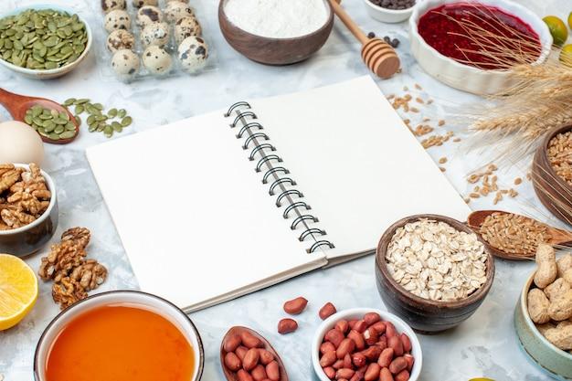 正面図開いたメモ帳、白い背景にゼリーの卵のさまざまなナッツと種子生地の色ナッツケーキ甘い砂糖パイハートの写真