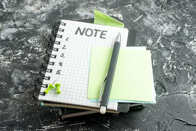 Blocco note aperto vista frontale con penna e nota di scrittura su sfondo grigio