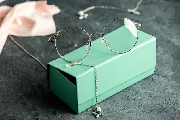 A front view optical sunglasses on the turquoise sunglasses box and grey desk with silver bracelets isolated sight vision eyes