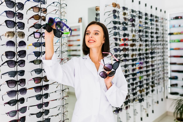 Front view of optician holding sunglasses pairs