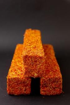 Вид спереди апельсиновый батончик конфетка вкуснятина вкусно на темном полу