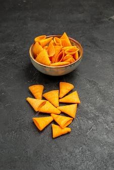暗い背景のスナックポテトコーンカラーにスパイシーペッパーと正面図オレンジチーズcips