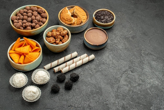 ダークグレーの背景に甘いナッツとチョコレートフレークの正面図オレンジ色のcips食事スナック朝食ナッツ