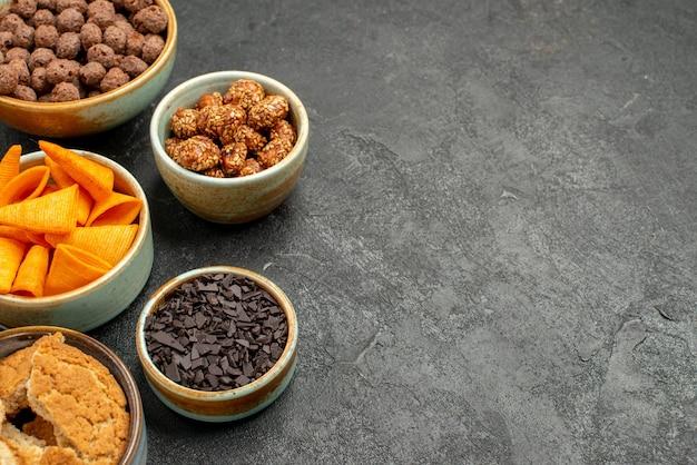 灰色の背景に甘いナッツとチョコレートフレークとオレンジ色のcipsの正面図食事スナック朝食ナッツ