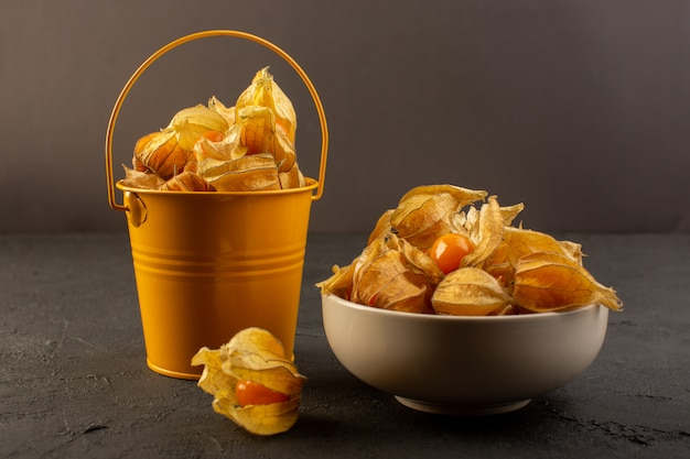 A front view orange fruits inside peels and yellow bucket isolated on dark