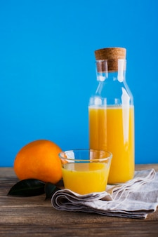 Front view orange juice bottle and glass