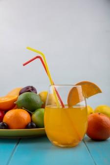 Vista frontale del succo d'arancia in un bicchiere con prugne ciliegia arance prugne limoni con calce su un piatto giallo