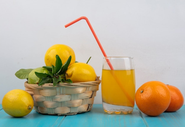Front view orange juice in a glass with a straw  oranges and lemons in a basket