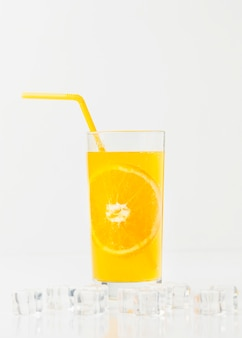 Front view of orange juice glass with straw