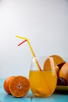 Vista frontale del succo d'arancia in un bicchiere con cannucce e arance