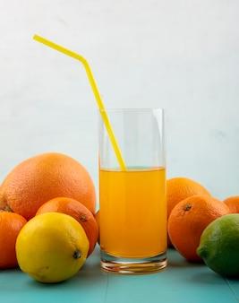 Vista frontale del succo d'arancia in un bicchiere e giallo paglierino con arance, pompelmo e limone con calce