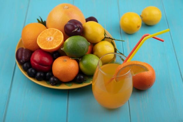ターコイズブルーの背景に黄色いプレートにライムとチェリープラムオレンジプラムレモンとグラスの正面図オレンジジュース