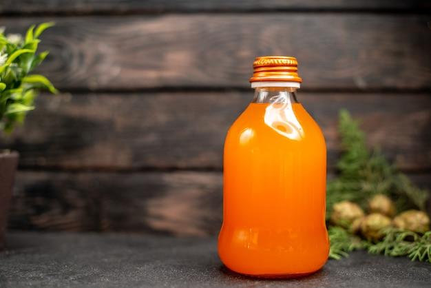 茶色の孤立した表面上のボトルの新鮮なオレンジの正面図オレンジジュース
