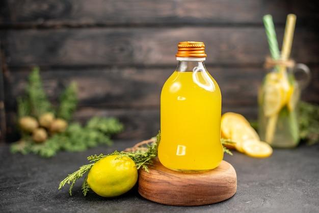 暗い木の表面に木の板レモンのボトルの正面図オレンジジュース