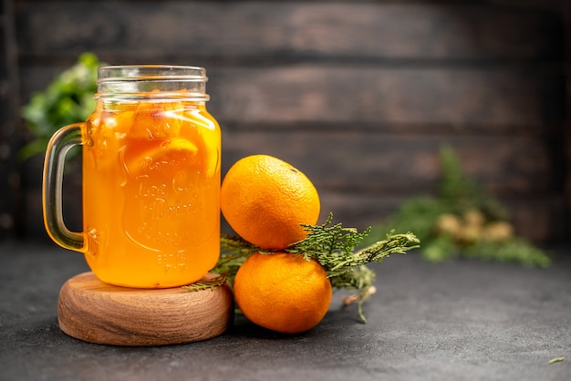 Front view orange lemonade in glass on wood board fresh oranges on brown isolated surface