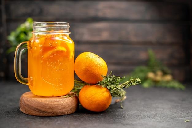 正面図木製ボード上のガラスのオレンジレモネード茶色の孤立した表面上の新鮮なオレンジ