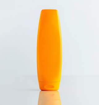 A front view orange shampoo bottle on the white wall