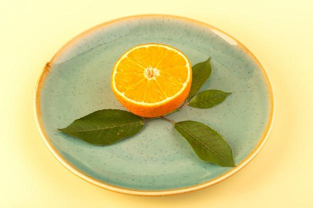 Una vista arancione fetta fresca fresca succosa dolce maturo con foglia verde all'interno della lastra di vetro isolato su sfondo color crema di agrumi di frutta verde