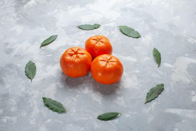 Vista frontale arancio mandarini interi agrumi sulla luce scrivania agrumi succo di frutta esotica
