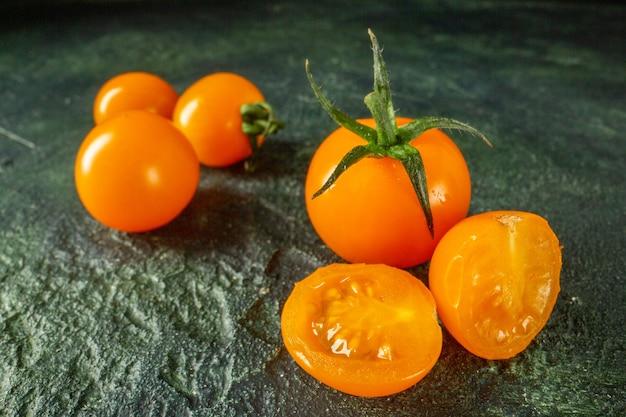 暗い表面の正面図オレンジトマト