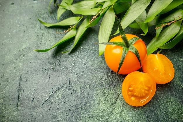 濃い緑色の表面に緑の葉を持つ正面図オレンジ色のトマト