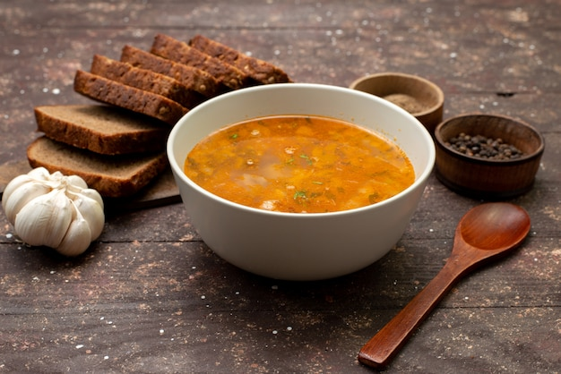 Front view orange vegetable soup with bread loafs and garlic on brown, food meal soup bread