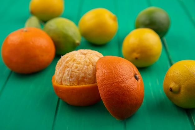 Апельсин вид спереди с очищенной кожурой на зеленом фоне