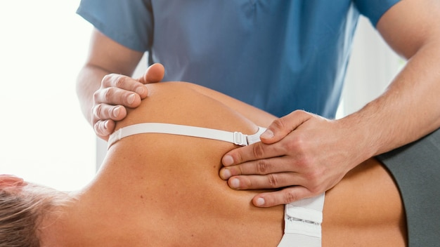 Front view of osteopathic therapist checking female patient's back
