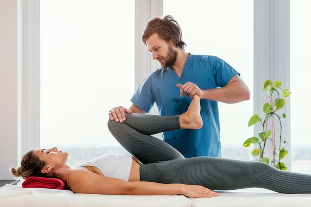 Front view of osteopathic therapist checking female patient's leg movement
