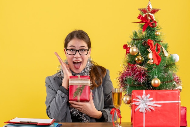 Vista frontale felicissima ragazza con gli occhiali seduto al tavolo che mostra la sua felicità albero di natale e regali cocktail