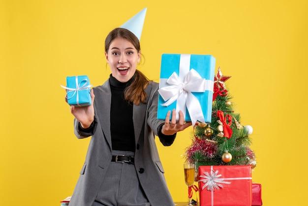 Ragazza felicissima di vista frontale con la protezione del partito che tiene i regali di natale vicino all'albero di natale e al cocktail dei regali