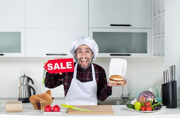 Vista frontale dello chef maschio felicissimo che tiene in mano il cartello di vendita e l'hamburger in cucina