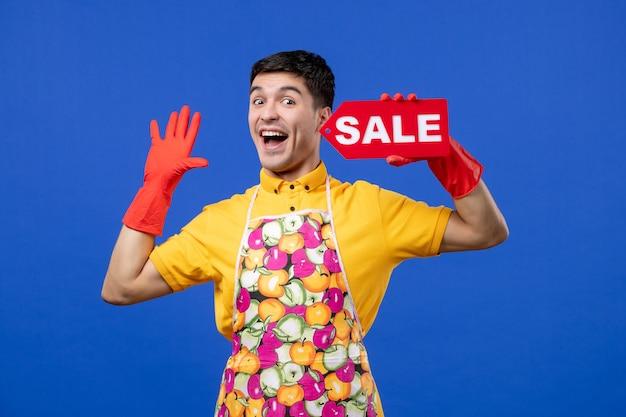 Vista frontale della governante maschio felicissima con i guanti di scarico che tengono il cartello di vendita rosso sulla parete blu