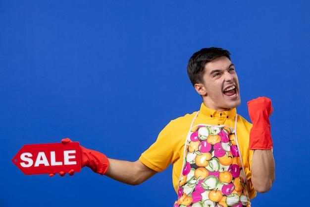 Vista frontale della governante maschio felicissima in maglietta gialla con cartello di vendita che mostra felicità sulla parete blu