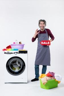 Vista frontale uomo felicissimo in grembiule che regge il cartello di vendita in piedi vicino al cesto della biancheria della lavatrice sul muro bianco