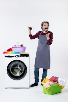 Vista frontale uomo felicissimo che regge la carta in piedi vicino al cesto della biancheria della lavatrice sul muro bianco