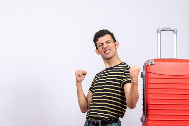 전면보기 줄무늬 티셔츠와 빨간 가방으로 기뻐 젊은 남자