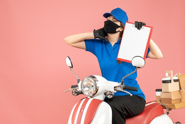 Front view of overtired courier woman wearing medical mask and gloves sitting on scooter holding empty paper sheets delivering orders on pastel peach background