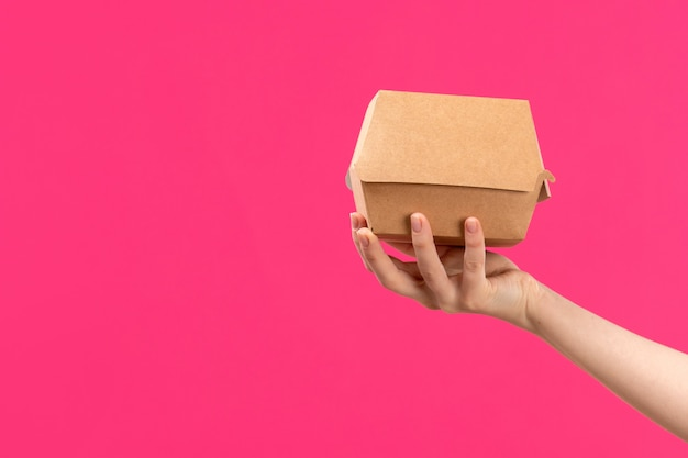 A front view package hand holding brown package female hand pink background color eat food