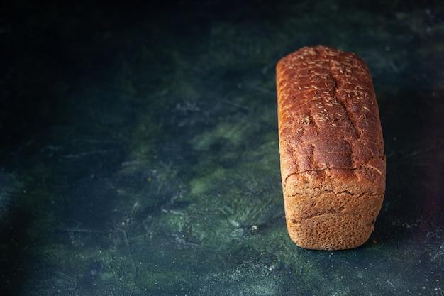 Vista frontale del pane nero confezionato sul lato sinistro su sfondo blu in difficoltà con spazio libero