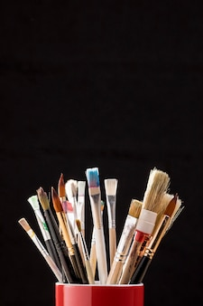 Front view of paint brushes in mug with copy space