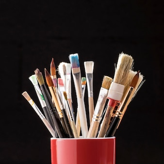 Front view of paint brushes in mugh