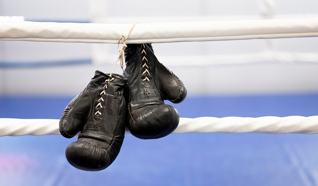 Front view of pair of boxing gloves next to ring
