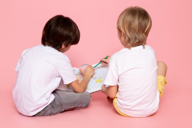 Front view pair of boys drawing map in white t-shirt on pink