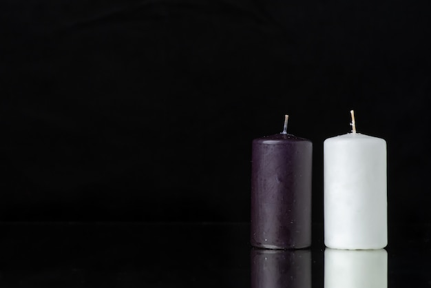 Front view of pair of candles on the black