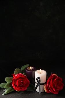 Vista frontale di coppia di candele fiori rossi su fondo nero